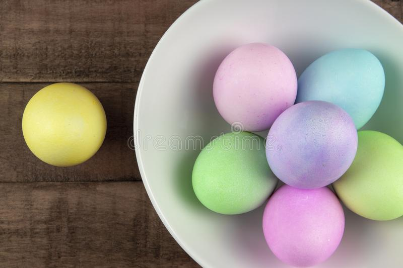 Overhead view of pastel painted easter eggs in a white bowl on rustic farm table stock photos