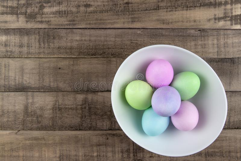 Overhead view of pastel painted easter eggs in a white bowl on rustic farm table stock photo