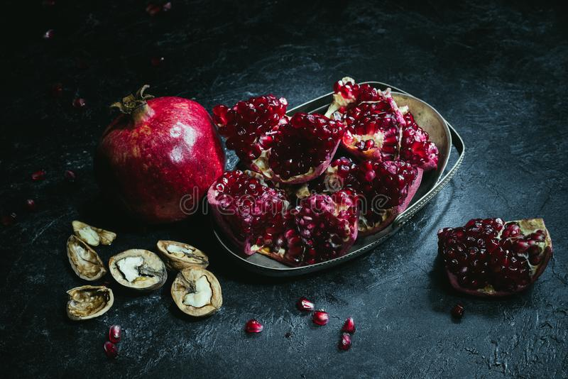 Overhead view of pomegranates in metal bowl and walnuts royalty free stock images