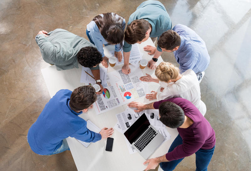Overhead view of professional businesspeople discussing and brainstorming together stock photography