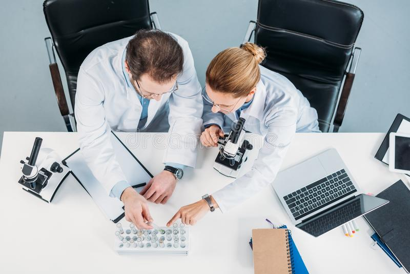 overhead view of scientific researchers in white coats looking at flasks with reagents at workplace stock image