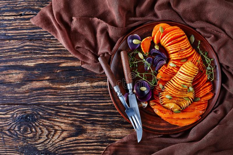 Overhead view of sliced Butternut squash. Sliced roasted halves of Butternut squash or pumpkin with red onion, thyme, pumpkin seeds and spices on an earthenware royalty free stock image