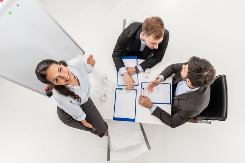 overhead view of smiling businesswoman looking up while colleagues having discussion at meeting royalty free stock photography