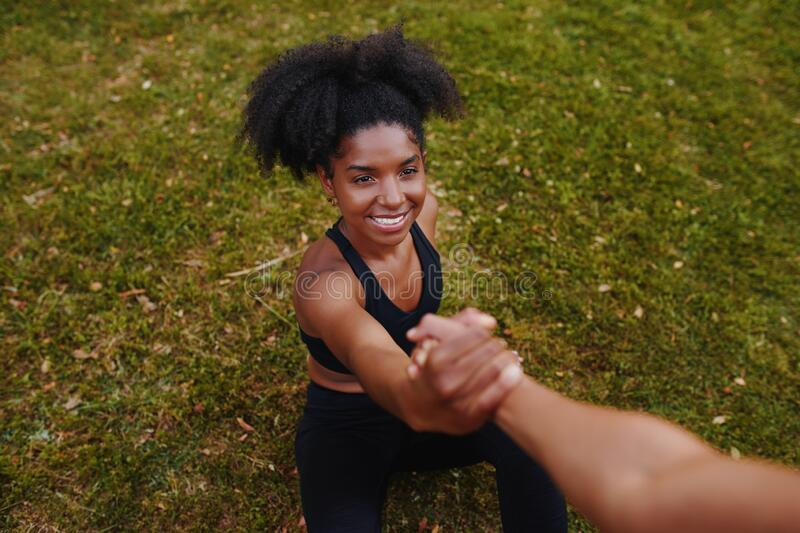 An overhead view of a smiling fitness young african american woman getting a helping hand from her friend after doing royalty free stock image
