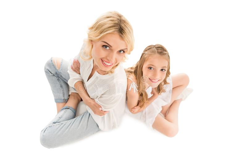 overhead view of smiling mother and preteen daughter looking at camera stock photos