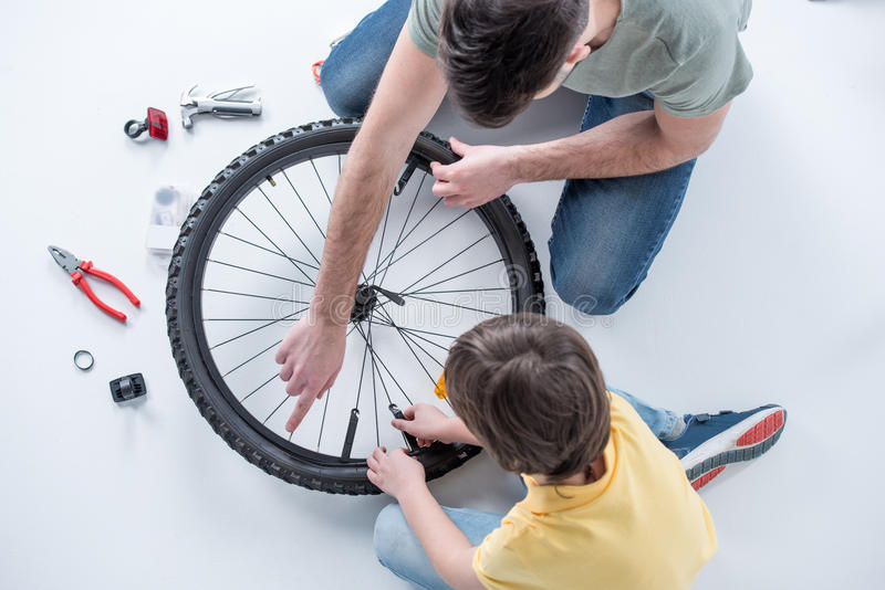 Overhead view of son and father repairing bicycle tire in studio. On white royalty free stock photo
