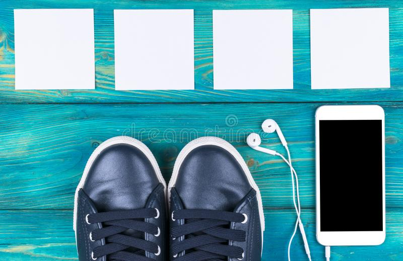Overhead view of sports shoes by mobile phone with isolated screen and in-ear headphones and white empty blank sheets. On black wooden table floor. Empty space royalty free stock images