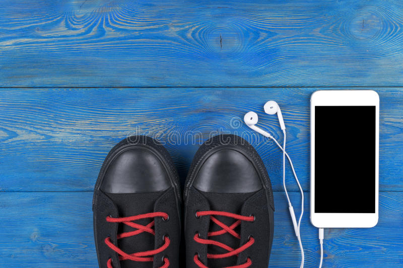 Overhead view of sports shoes by mobile phone with screen and in-ear headphones on blue wooden table, floor. Empty space royalty free stock images