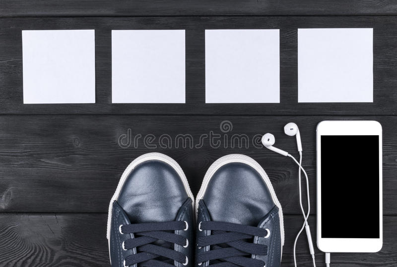 Overhead view of sports shoes by mobile phone with screen and in-ear headphones and white empty blank sheets on black. Wooden table, floor. Empty space for text stock photo