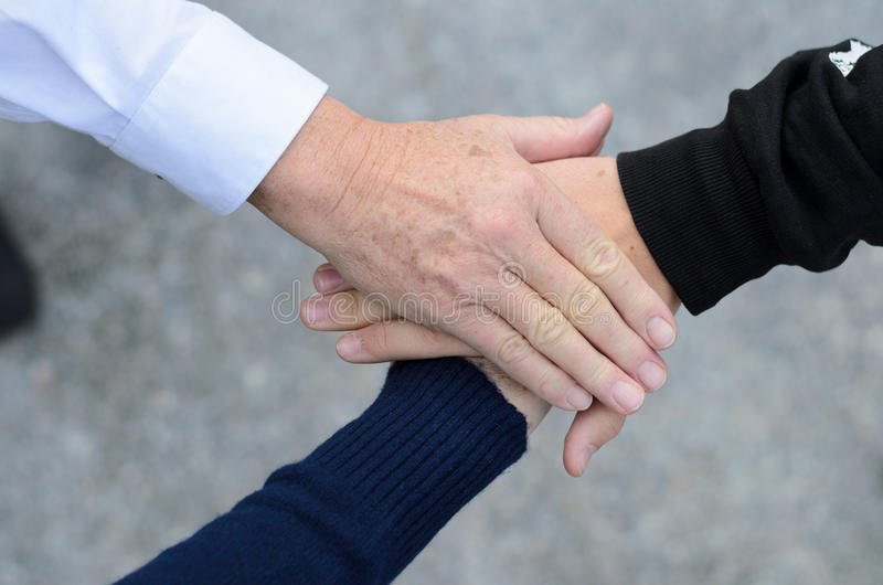 Overhead view of three hands clasped together royalty free stock photo