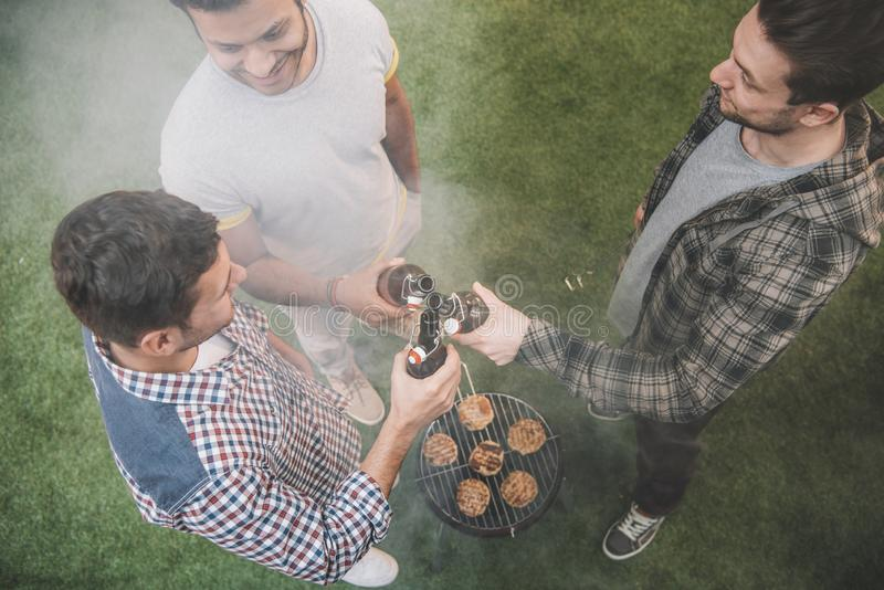Overhead view of three young men making barbecue and clinking royalty free stock images