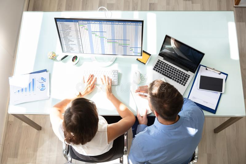 Two Businesspeople Analyzing Gantt Chart On Computer royalty free stock photos