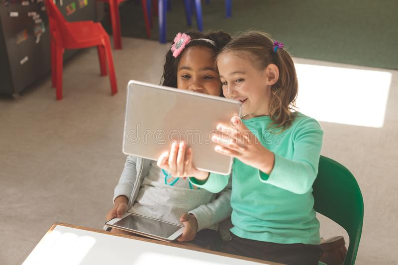 Overhead view of two school girls taking a photo with a digital tablet stock photography