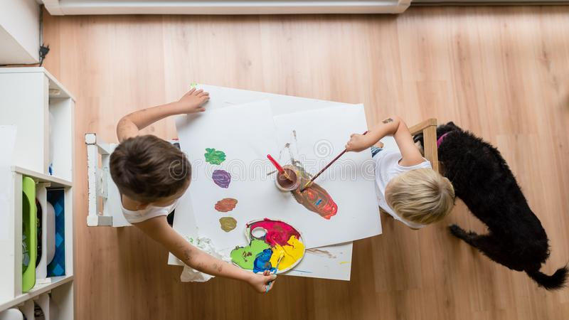 Overhead view of two toddler children painting with water colour stock photo