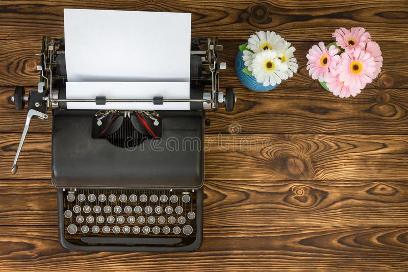 Overhead view of typewriter next to flowers. Overhead view of vintage metal typewriter next to blue and pink flowers sitting on wooden plank table stock photos