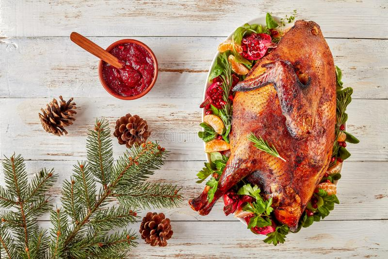 Overhead view of a whole roasted free-range turkey on a white oval plate with greens, pomegranates and tangerines, cranberry sauce stock photos