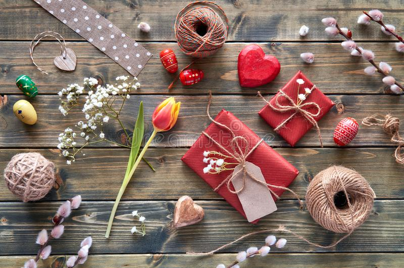 Overhead view of wooden table with springtime decorations, wrapped gifts, willow and tulip flowers and Easter eggs royalty free stock photos