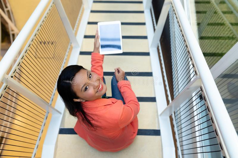 Businesswoman holding digital tablet on stairs royalty free stock images