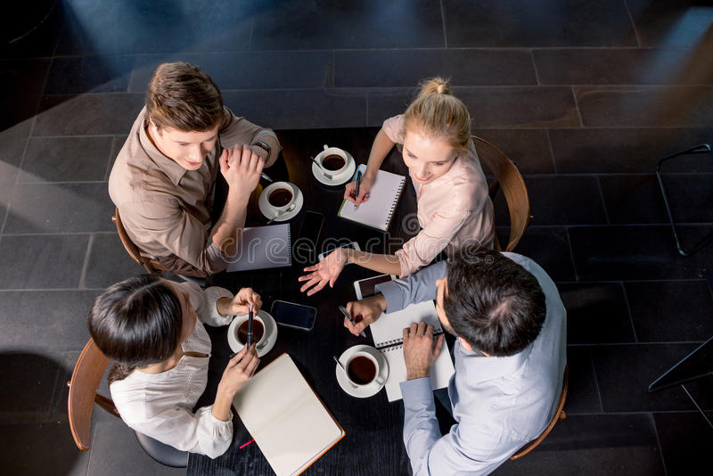 Overhead view of young businesspeople discussing project at table with cups of coffee stock photo