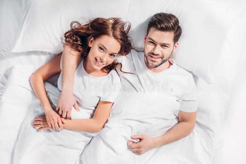 overhead view of young smiling couple in love lying on bed under stock photo