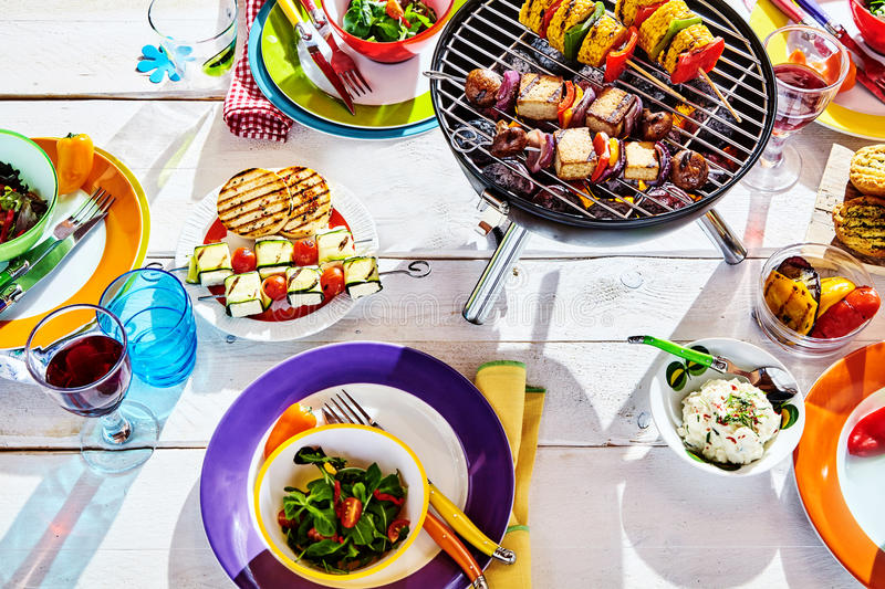 Overhead Well Laid summer table with colorful dish and brazier. Overhead Well Laid summer table with colorful dish and plates and brazier on white background royalty free stock photo