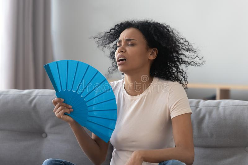 Overheated african young woman feeling hot waving fan at home. Overheated african young woman feeling hot waving fan annoyed with high temperature sit on sofa at stock photography