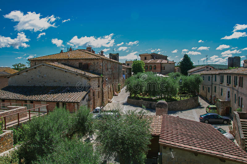 Overiew of buildings and trees in the city center of the Monteriggioni hamlet. A medieval fortress, surrounded by stone walls, at the top of a hill, near Siena royalty free stock photos