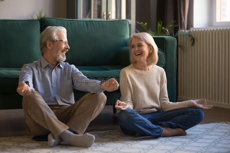 Smiling elderly couple sit on floor meditating at home stock image