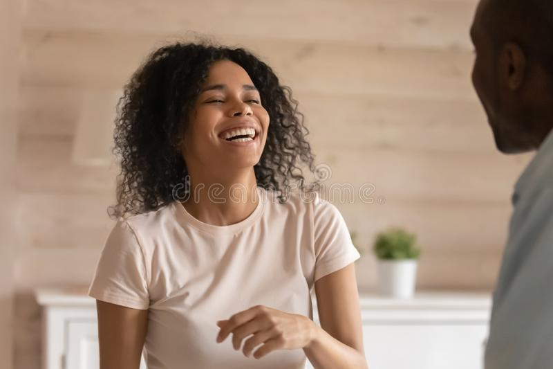 Happy african American woman laugh talking with husband. Overjoyed african American young wife laugh talking chatting with husband or friend, happy biracial royalty free stock images