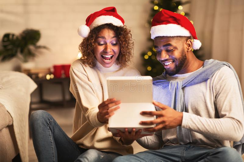 Overjoyed afro couple open xmas box and looking inside. Enjoying Christmas eve stock photos