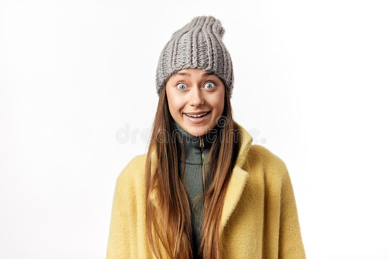Beautiful bug eyed woman expresses happy emotions, has broad pleasant smile, dressed in warm topcoat and fashionable hat royalty free stock image