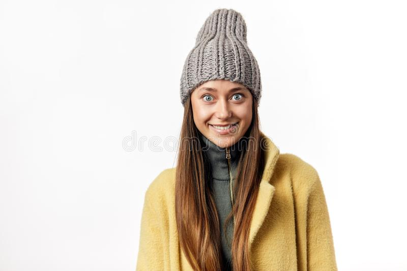 Beautiful bug eyed woman expresses happy emotions, has broad pleasant smile, dressed in warm topcoat and fashionable hat stock images