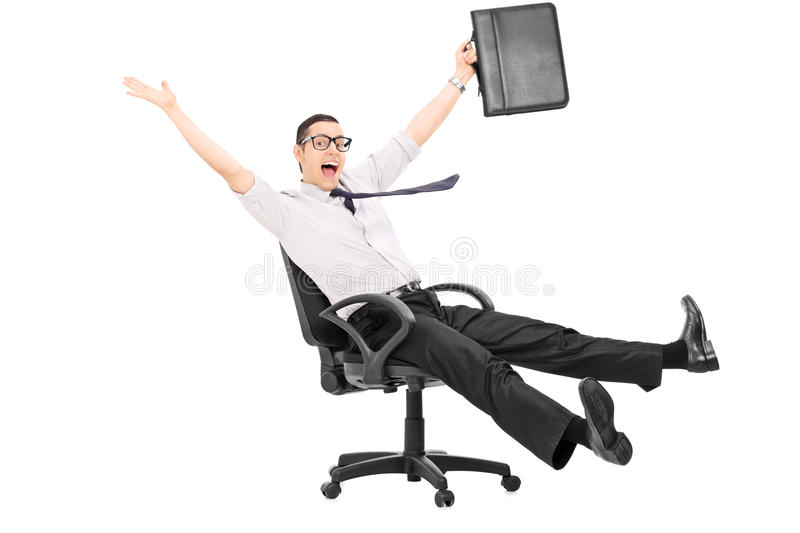 Overjoyed businessman riding in an office chair royalty free stock photography