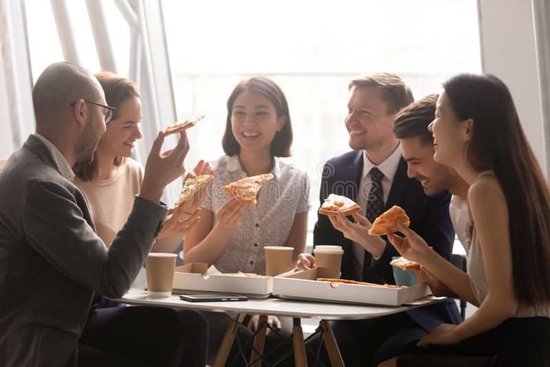 Overjoyed company multiracial staff employees gathered for lunch meal. stock images