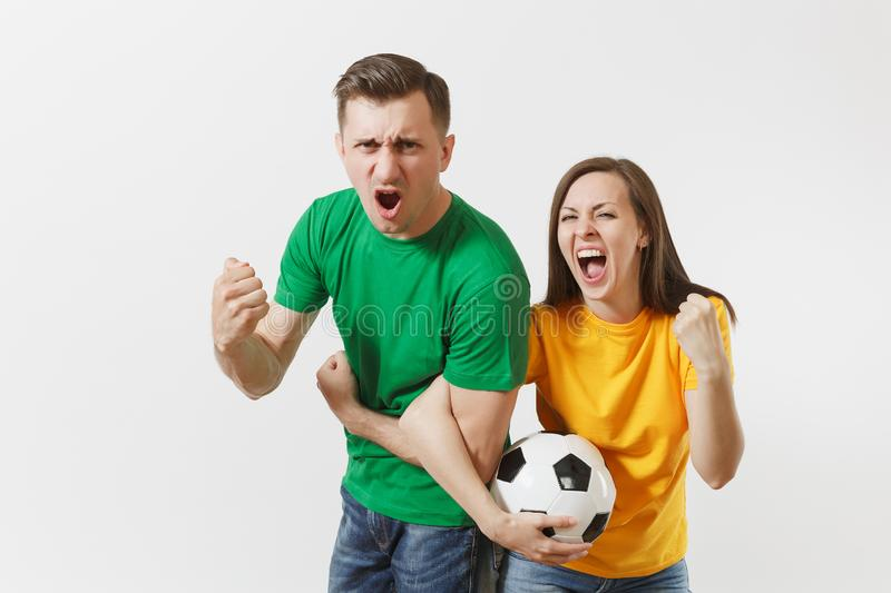 Overjoyed couple, woman man, football fans in yellow green t-shirt cheer up support team with soccer ball doing winner. Overjoyed couple, women man, football royalty free stock image