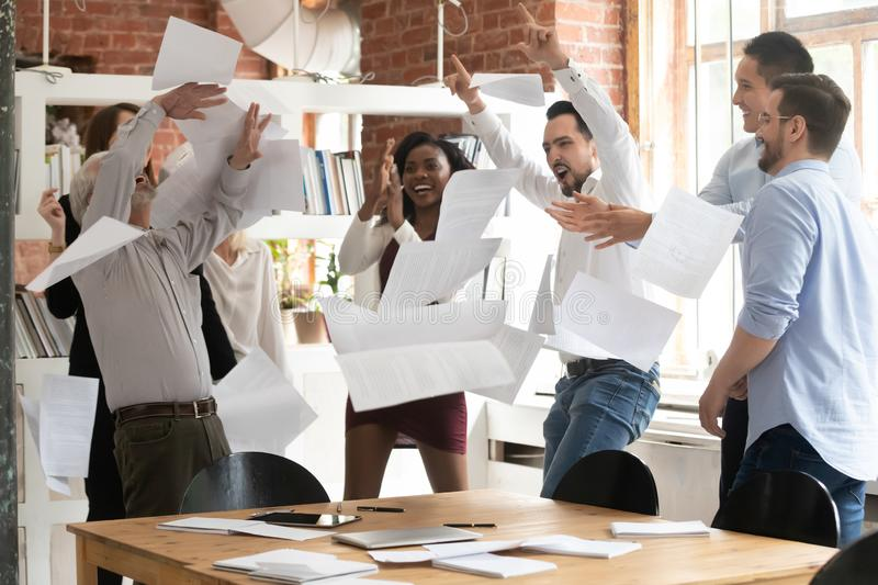Overjoyed diverse employees throw papers celebrating success. Overjoyed multiracial businesspeople throw paper handout materials up in air celebrating successful royalty free stock photography