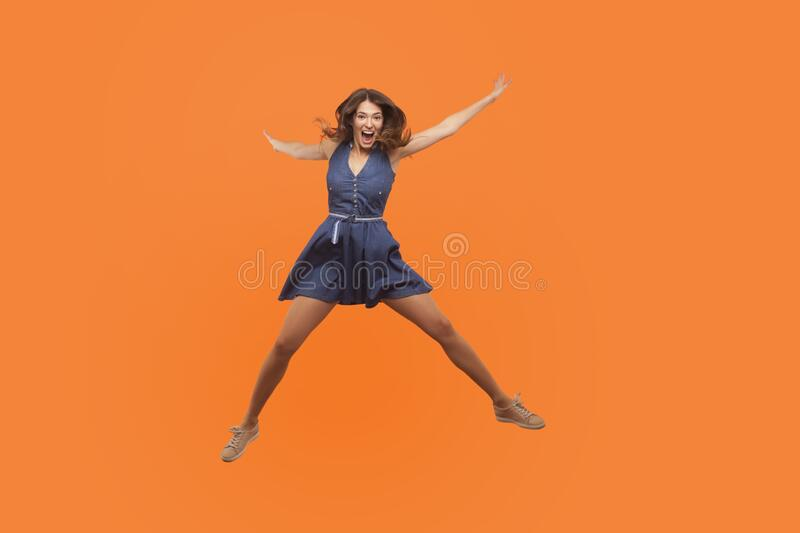 Overjoyed excited ecstatic brunette woman in denim dress jumping up like star and shouting from enthusiasm. Flying isolated on orange background, full of happy royalty free stock photos