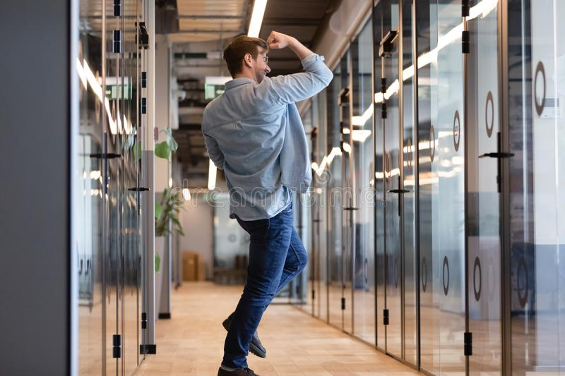 Overjoyed funny young business man jumping in hallway celebrating victory. Overjoyed funny young business man jumping in hallway celebrate success victory win stock photo