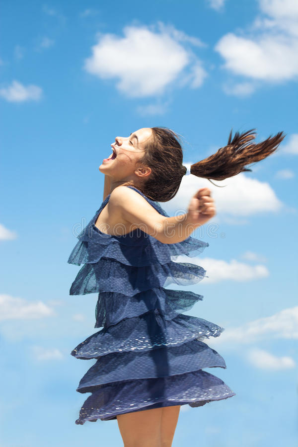 Overjoyed girl in blue dress spin summer day. Happy smiling girl in blue dress spin around summer day against blue sky stock photo