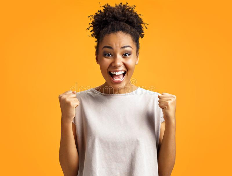 Overjoyed girl clenches fists with happiness, widely opens mouth as shouts loudly. Photo of african american girl wears casual outfit on orange background royalty free stock photo