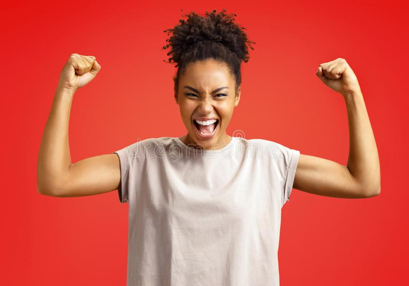 Overjoyed girl clenches fists in triumph. Photo of african american girl royalty free stock images