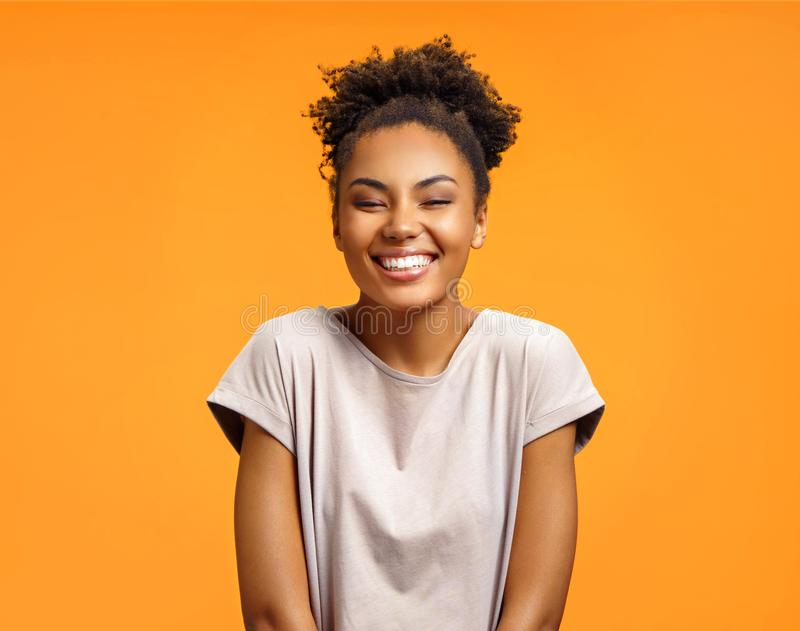 Overjoyed girl with curly hairstyle laughs happily. Photo of african american girl wears casual outfit on orange background. Emotions and pleasant feelings stock images