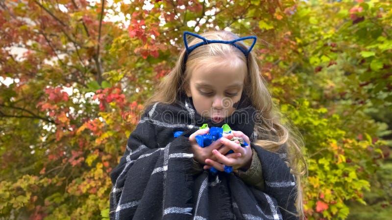 Overjoyed girl holding candies, making funny face, enjoying Halloween holiday royalty free stock photos