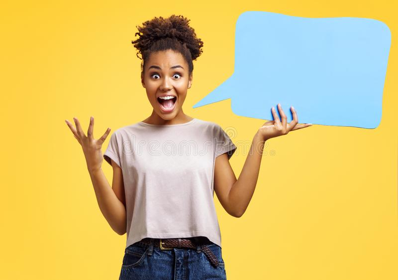 Overjoyed girl holds blue speech bubble board. Photo of african american girl wears casual outfit on yellow background. Emotions and pleasant feelings concept stock photography