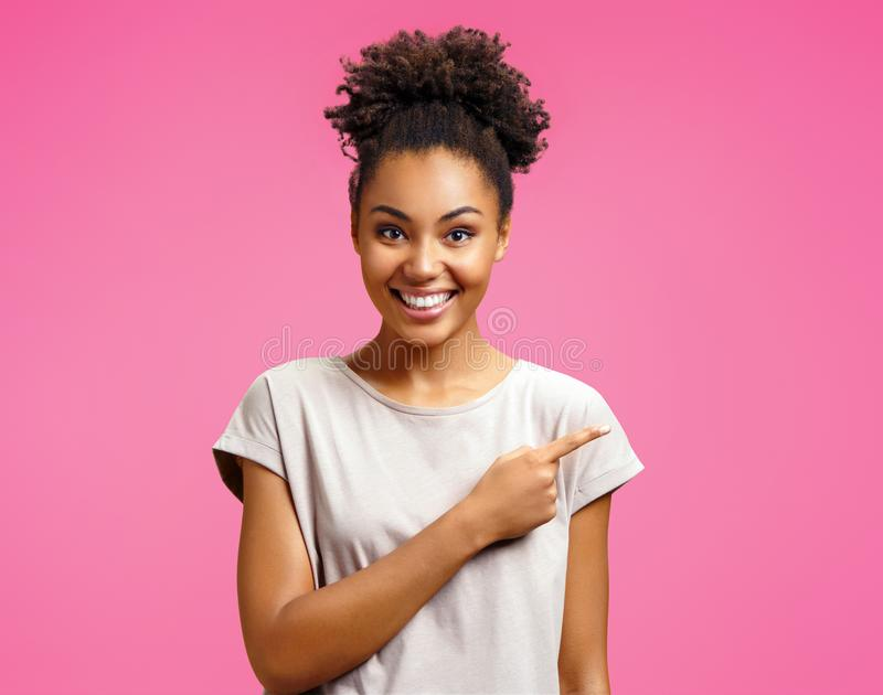 Overjoyed girl points aside, shows something at freespace. royalty free stock image