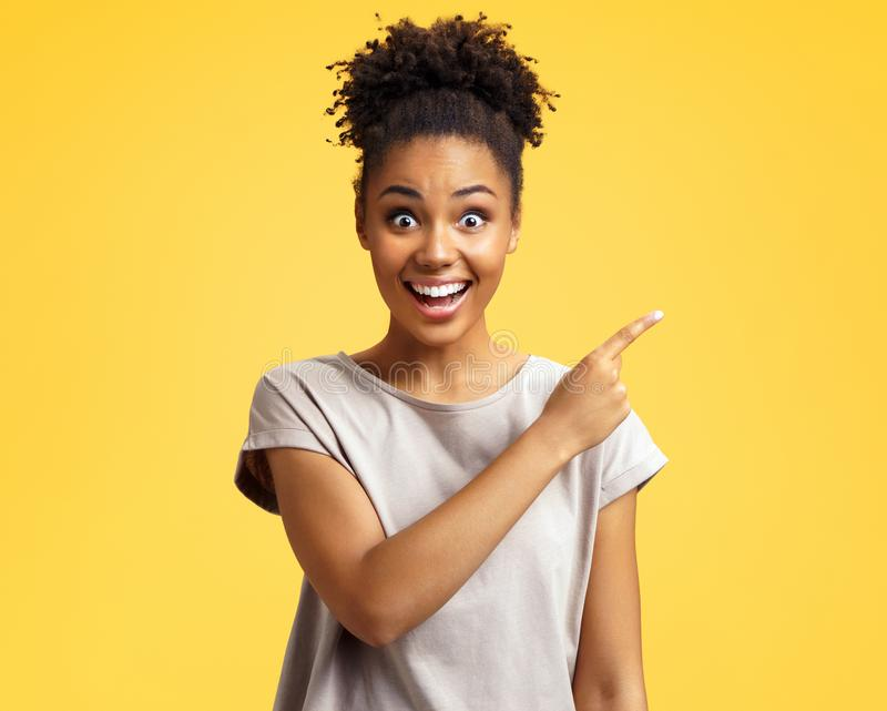 Overjoyed girl points aside, shows something at freespace. royalty free stock photo