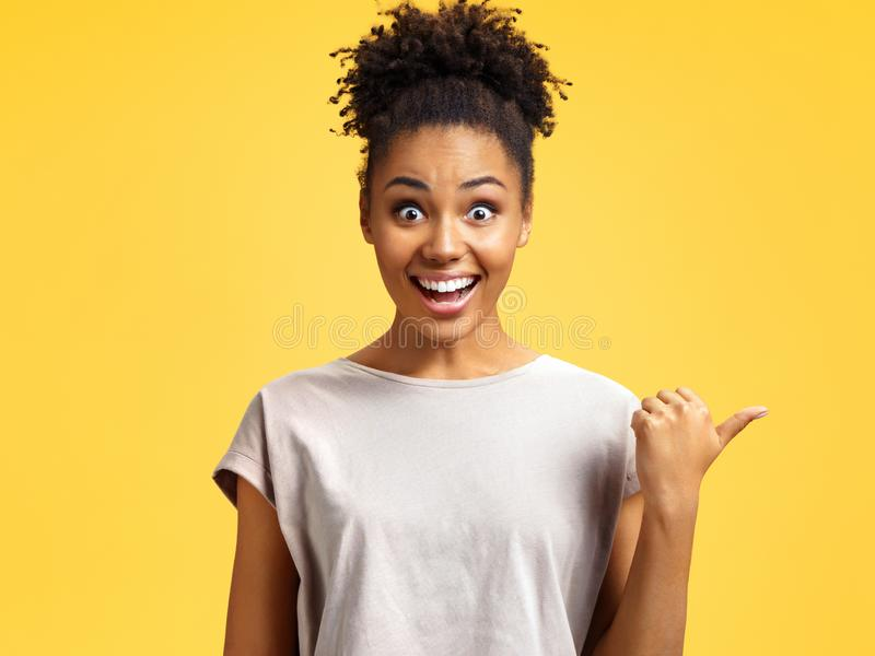 Overjoyed girl points aside, shows something at freespace. royalty free stock images