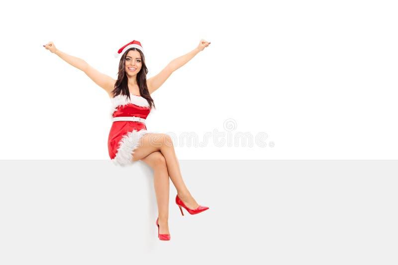 Overjoyed girl in Santa costume sitting on a panel stock photo