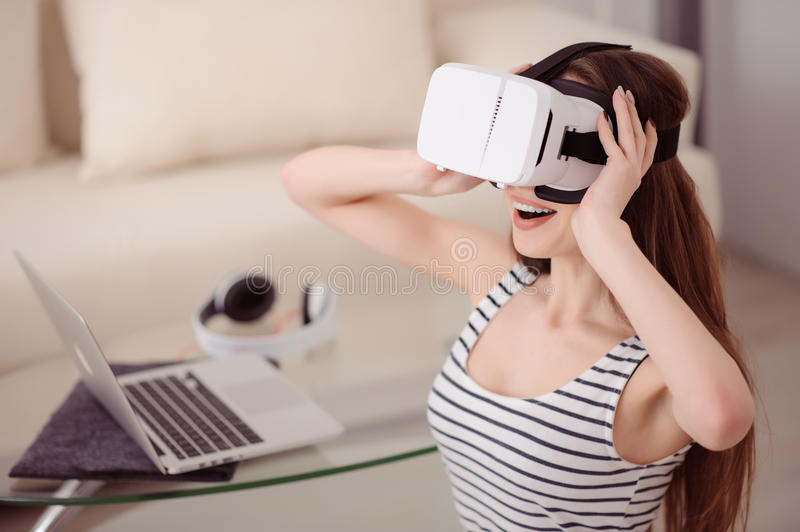 Overjoyed girl wearing virtual reality device royalty free stock photography