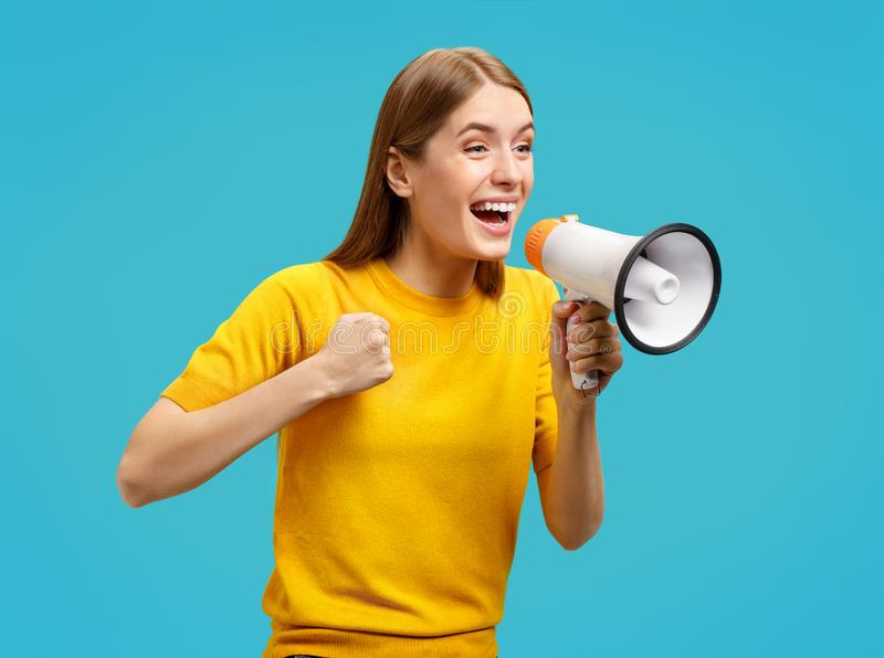 Overjoyed girl in yellow sweater shouts loudly into megaphone royalty free stock image